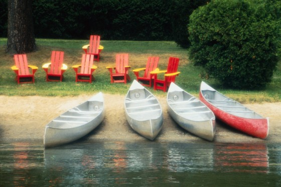 Canoes and Chairs on the Shore of a Lake
